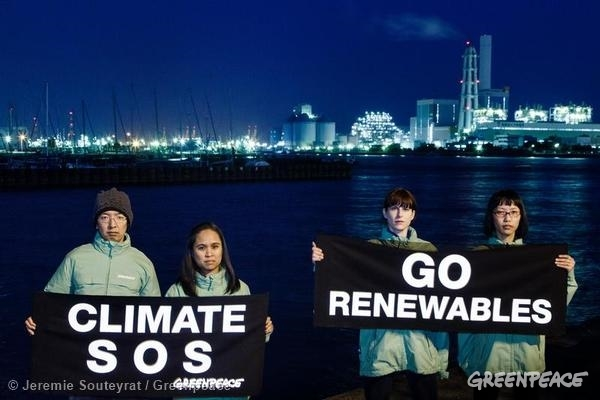 Greenpeace activists display messages reading 'Climate SOS' and 'Go Renewables' outside the Isogo coal power plant and the Minami-Yokohama gas power plant near where the IPCC is meeting.