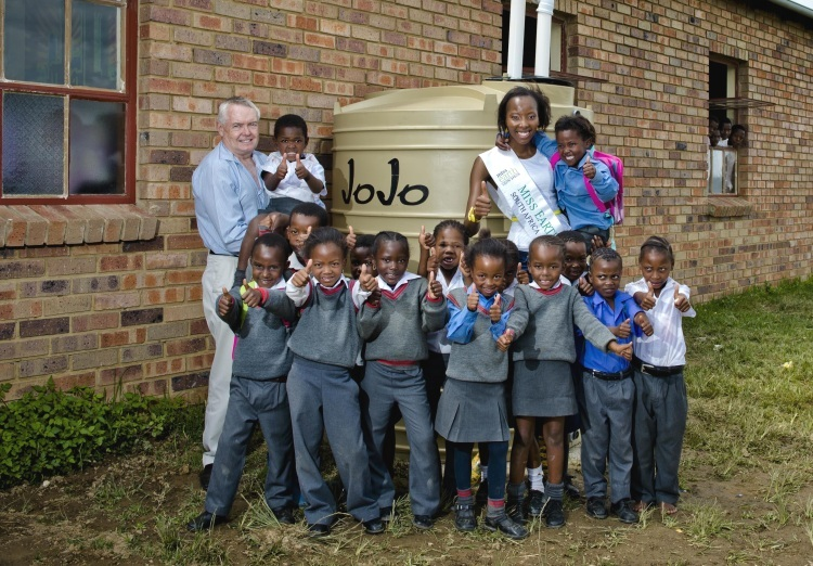 Rod Cairns (MD JoJo Tanks) and Ashanti Mbanga with learners at Solwazi Primary in Orange Farm