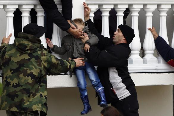Serbian army soldiers evacuate a boy from a flooded house in town of Obrenovac, east from Belgrade