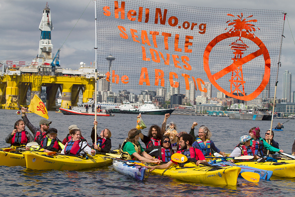 SEATTLE, WA - MAY 14:  Environmental activists in kayaks protest the arrival of the Polar Pioneer, an oil drilling rig owned by Shell Oil, on May 14, 2015 in Seattle, Washington. The rig is part of a fleet that will lead a controversial oil-exploration effort off Alaska's North Slope.  (Photo by Karen Ducey/Getty Images)