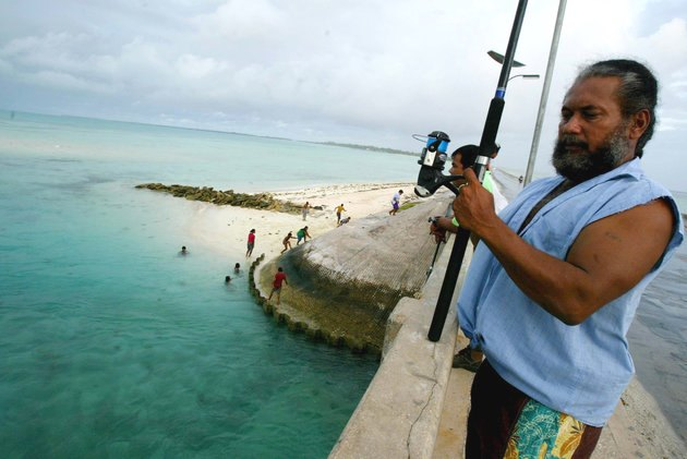 In this March 30, 2004 file photo a man fishes on a bridge on Tarawa atoll, Kiribati. Fearing that climate change could wipe out their entire Pacific archipelago, the leaders of Kiribati are considering an unusual backup plan: moving the populace to Fiji. (AP Photo/Richard Vogel)