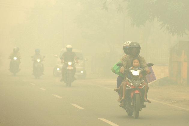 Motorists ride on a road as thick haze from forest fires shroud the city in Palangkaraya, Central Borneo, Indonesia, Tuesday, Oct. 27, 2015. The haze has blanketed parts of western Indonesia for about two months and affected neighboring countries like Singapore, Malaysia and Thailand. (AP Photos)